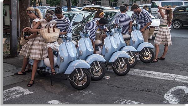 foto com diversos jovens vestidos como na década de 50, com motocicletas azuis do tipo vezpa enfileiradas