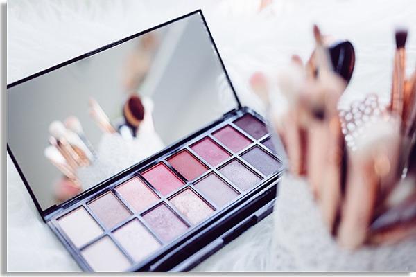 ilustração mostrando mesa de maquiagem branca, com estojo com maquiagens de diversas cores