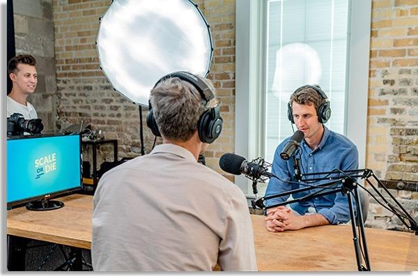 dois homens sentados de frente à uma mesa de madeira com microfones conversando