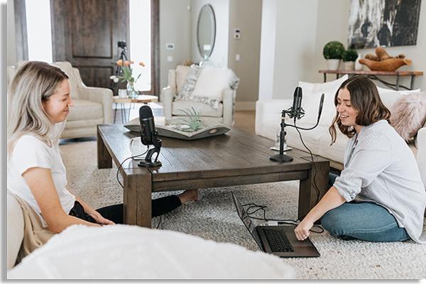 foto de duas mulheres sentadas no chão de uma sala, com microfones em uma mesa de madeira e um notebook no chão, como se estivessem a criar podcasts