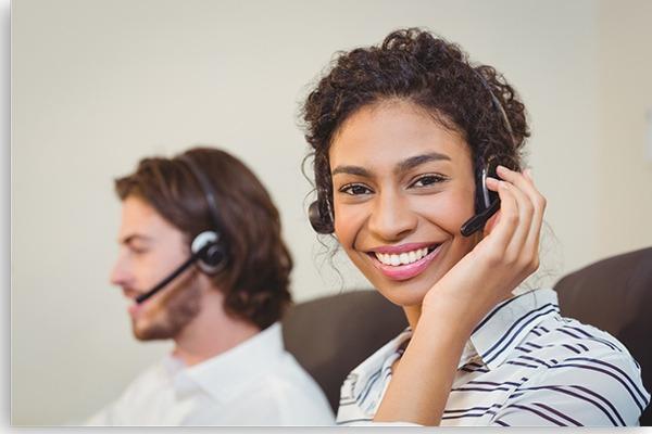 mulher negra e homem branco ao fundo fazendo atendimento por telefone