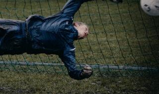 goleiro pulando em direção à bola